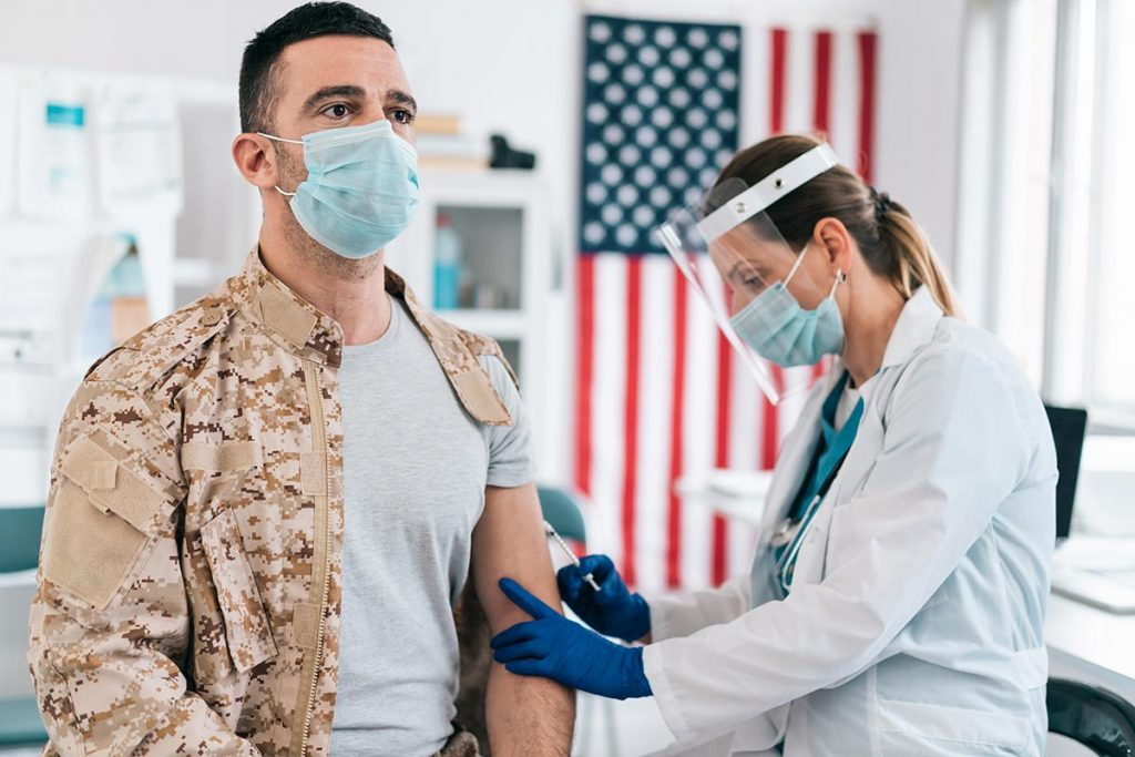 A man in a military uniform receives a vaccine. The military is looking for volunteers to help spot COVID-19 early.