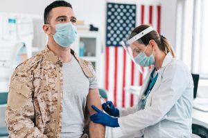 A man in a military uniform receives a vaccine