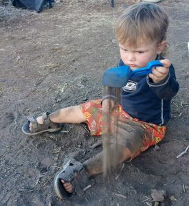 young child playing in the dirt.