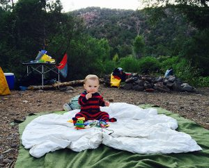 toddler sitting on a blanket at a camp site. blanket is a great tip when camping with kids.