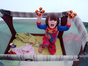 child holding up toys in a pack in play while on a camping trip.