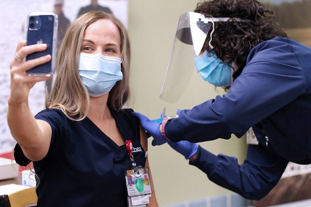 UCHealth employee takes a selfie while she gets her first dose of the COVID-19 vaccine in December 2020.