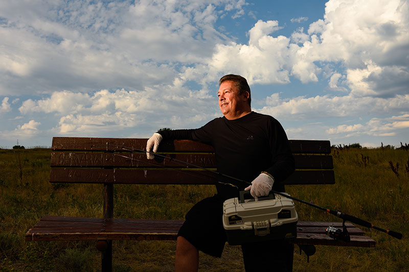 56-year-old man sitting on a bench with his fishing tackle will be one of those who get a third dose of COVID-19 vaccine because he had a liver transplant..