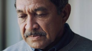 Breakthrough symptoms of COVID-19 can be milder than original COVID-19 infections. Here a Latino man looks serious.