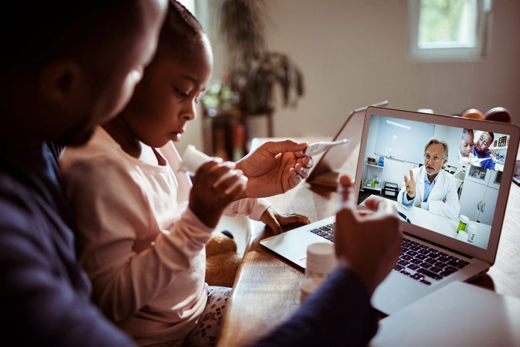 A man and a child visit with a medical provider virtually.