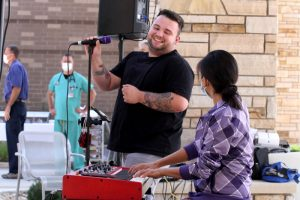 Jacob Larson, a young COVID survivor, sings to health care workers in a hospital courtyard