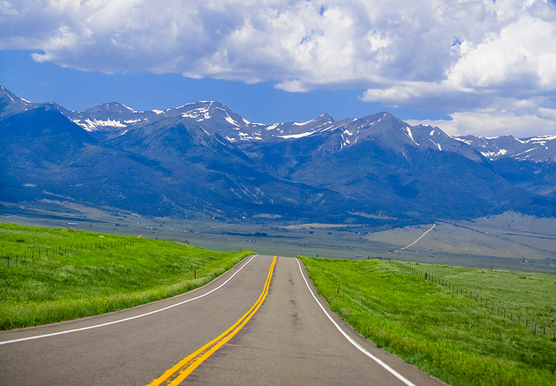 Colorado Scenic Byways lead you to great discoveries. Here a paved road leads to the snow-covered Wet Mountains in southern Colorado.