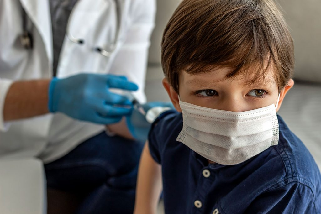 A boy wearing a mask receives a shot in his right arm.