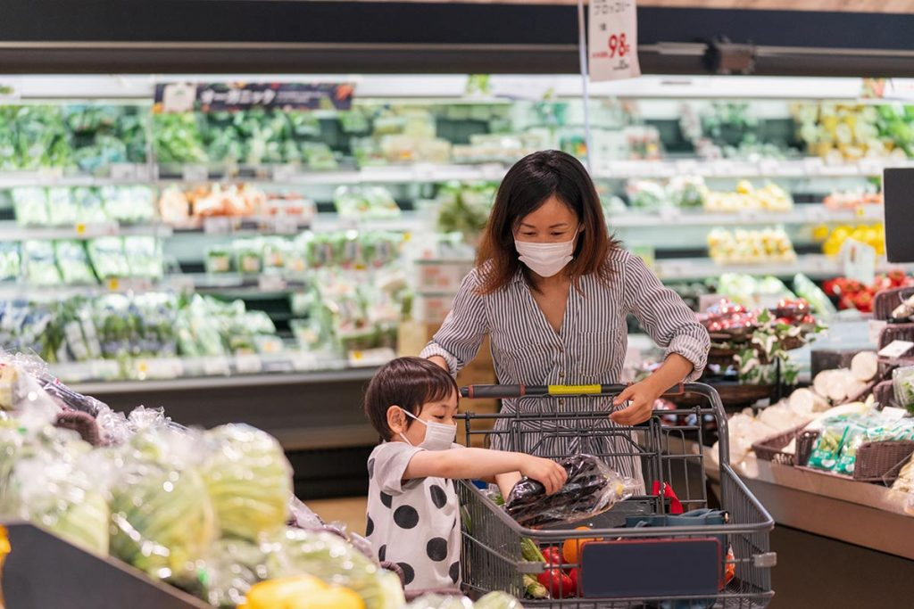 A woman and child figuring out what to buy at Asian market they are at..