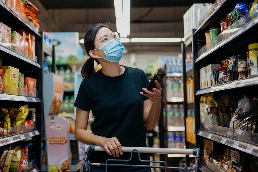 woman looking at her phone to know what to buy at Asian market she is shopping at.