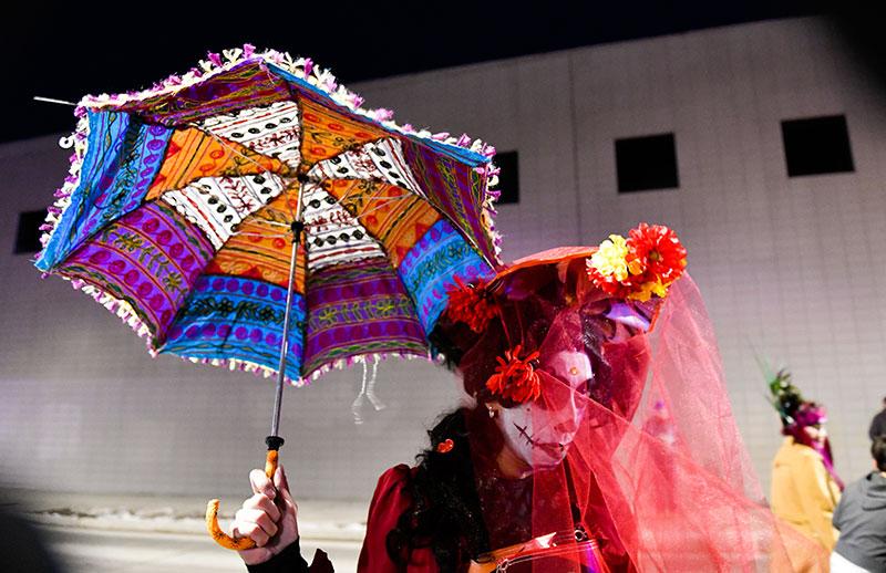 Una mujer con un velo de colores y una sombrilla celebra el Día de Muertos.