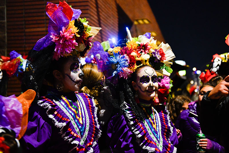 Young girls dress in bright colors to celebrate Day of the Dead in Denver.