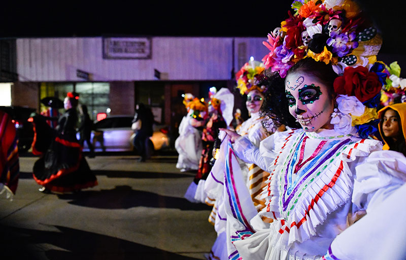 Young girls participate in a Day of the Dead parade in Denver.