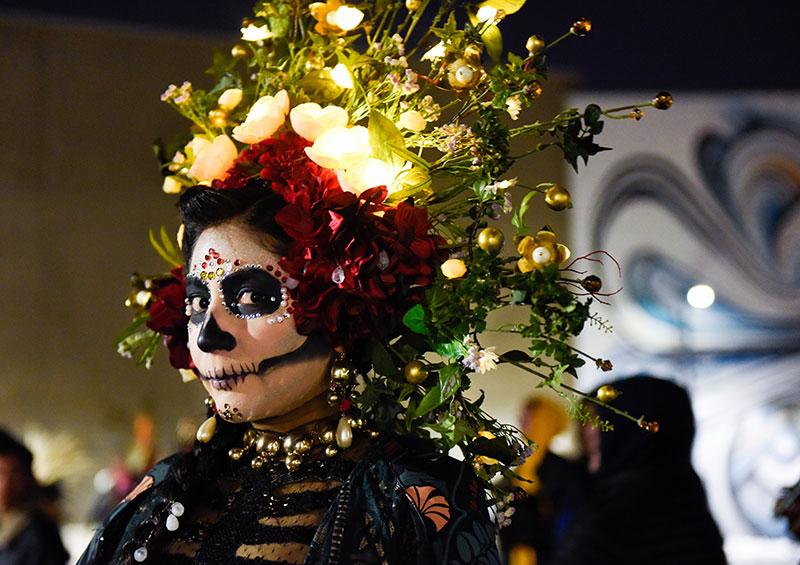 Una joven viste un elaborado disfraz para celebrar el Día de Muertos o Día de los Muertos en Denver.